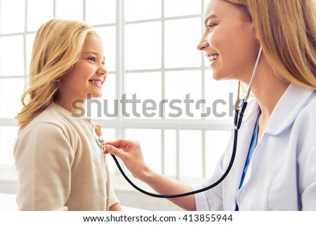 Beautiful young pediatrician is sounding little girl lungs. Both are smiling, sitting in doctors office - stock photo