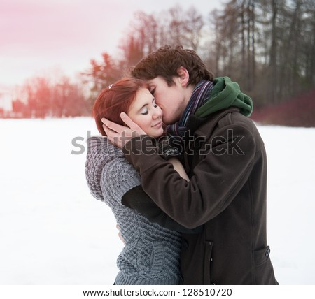 Beautiful young people embracing the winter outdoors. - stock photo