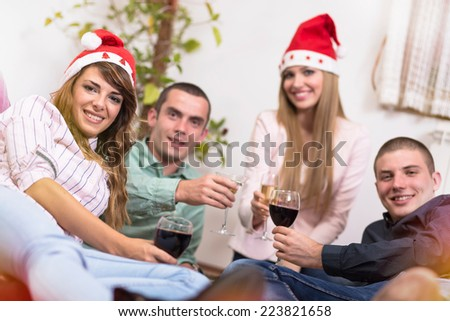 Beautiful young people having a Christmas toast - stock photo