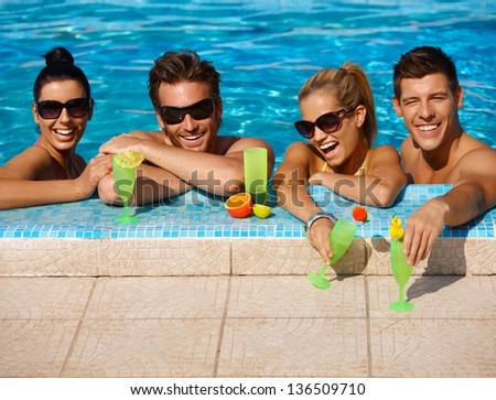 Beautiful young people having fun in swimming pool, drinking cocktail, smiling.