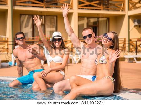 Beautiful young people having fun in swimming pool, smiling. - stock photo