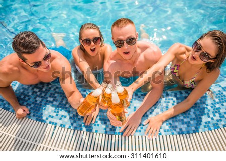 Beautiful young people having fun in swimming pool, smiling and drinking beer. - stock photo