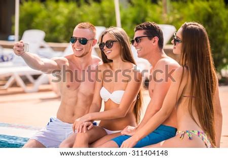 Beautiful young people having fun in swimming pool, smiling and making selfie. - stock photo