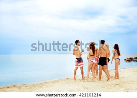 Beautiful young people having fun on beach - stock photo