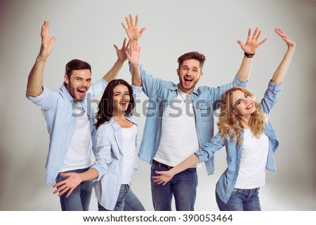 Beautiful young people in jeans are happy and playful, stretching hands, looking at camera and smiling, on a gray background