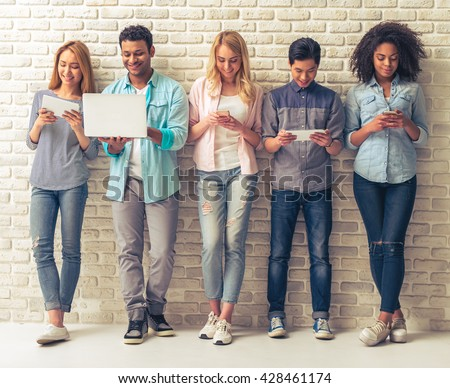 Beautiful young people of different nationalities are using gadgets and smiling, standing against white brick wall - stock photo