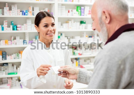 Beautiful young pharmacist selling medications to senior patient
