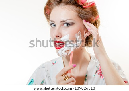 Beautiful young pinup woman shaving face looking in camera isolated on white background - stock photo