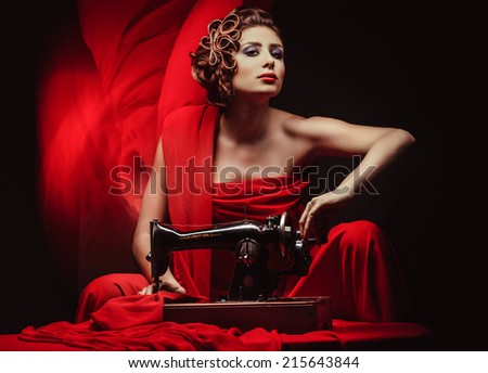 beautiful young pinup woman with sewing machine in red material - stock photo