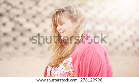 Beautiful young plus sized blonde caucasian teenage girl giggling as she walks along the beach with the sun creating flare from behind her - stock photo