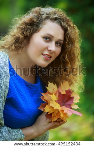 beautiful young plussize model in the autumn park with yellow leaves in her hands