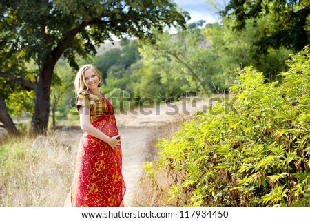 Beautiful young, pregnant Indian woman in traditional clothes with bridal makeup and jewelry. - stock photo