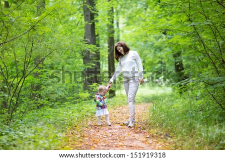 Beautiful young pregnant woman and her baby daughter walking in a sunny forest - stock photo