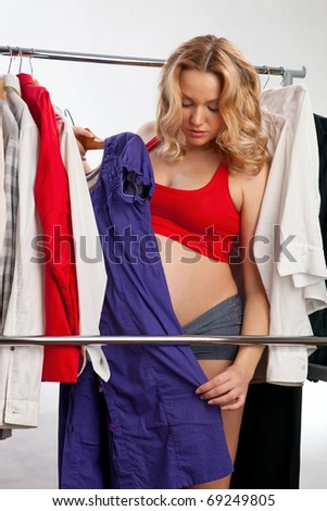 Beautiful young pregnant woman choosing what to put on - stock photo
