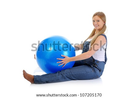 Beautiful young pregnant woman does sport exercises with a blue ball. Isolated on white background