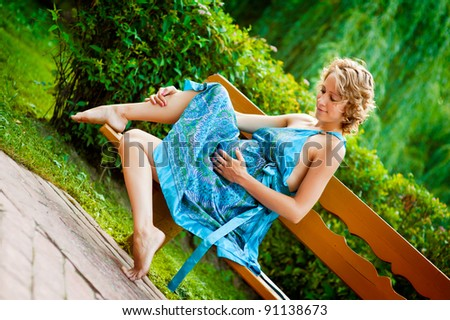Beautiful young pregnant woman in blue dress sitting on bench and holding belly - stock photo