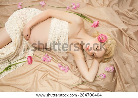 Beautiful young pregnant woman in lace fabric dreaming with flowers lying around - stock photo