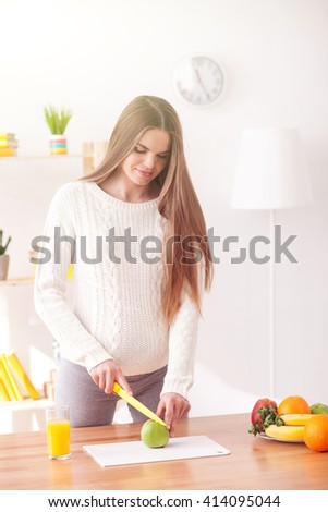 Beautiful young pregnant woman is preparing breakfast
