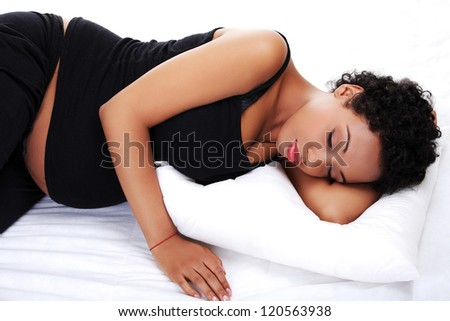 Beautiful young pregnant woman lying on bed