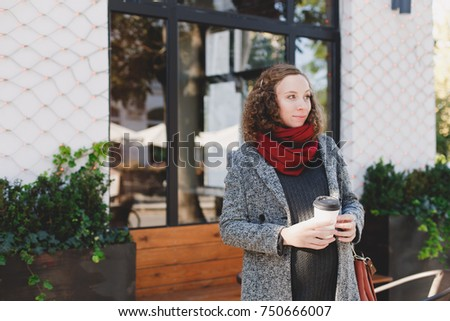 Beautiful young pregnant woman wearing sweater, jeans, grey coat and red scarf standing outside a cafe with a beautiful exterior and drinking take away coffee in the winter. Christmas, New Year mood.