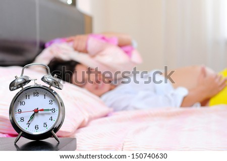 beautiful young pregnant woman with alarm clock in bed at home