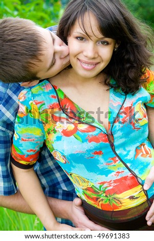Beautiful young pregnant woman with husband outdoor set - stock photo