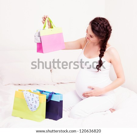 beautiful young pregnant woman with shopping bags and baby's clothes in bed at home - stock photo