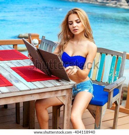 Beautiful young pretty blonde woman outdoor summer portrait having fun on seashore smiling sitting in restaurant choosing meal in menu
