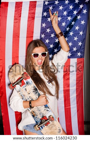 beautiful young pretty woman in sunglasses with national usa flag in background