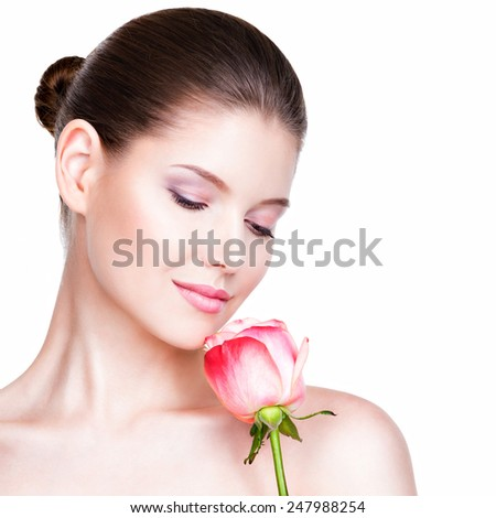 Beautiful young pretty woman with healthy skin and pink rose near face - isolated on white. - stock photo