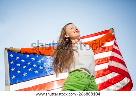 Beautiful young pretty woman with national usa flag over blue sky, backlight, focus on face - stock photo