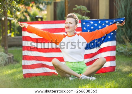 Beautiful young pretty woman with national usa flag over green natural background, soft image