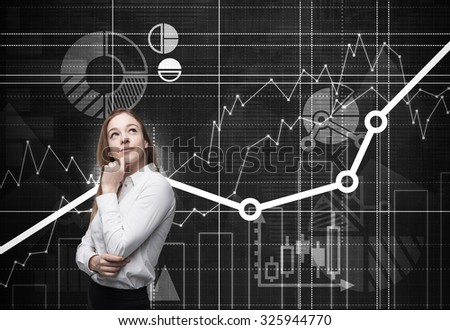 Beautiful young professional with the hand which holds her chin is thinking about future opportunities of the project. Financial analytic charts are drawn on the background. - stock photo
