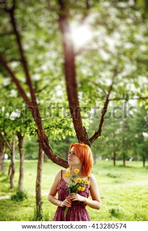 Beautiful Young Red Hair Woman Holding Spring Flowers in Park. Blurred Background. - stock photo