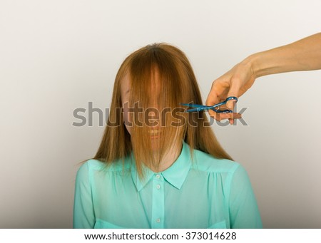 Beautiful young red-haired girl at the hairdresser makes blow drying, shorn bangs, hair polishing - stock photo
