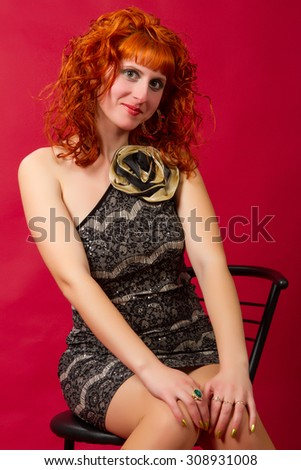 beautiful young red-haired girl  in an elegant dress on a red background