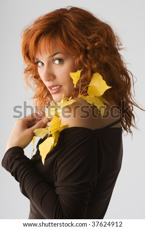 beautiful young red haired woman with yellow autumn leaves near her face