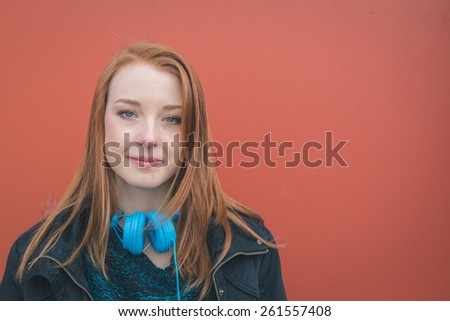 Beautiful young redhead girl posing in the city streets - stock photo
