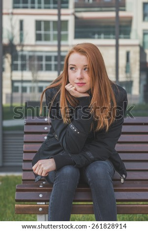Beautiful young redhead girl posing in the city streets. Instagram style. - stock photo