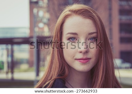 Beautiful young redhead girl posing in the city streets. Instagram style.