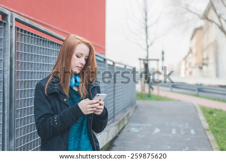 Beautiful young redhead girl texting in the city streets - stock photo