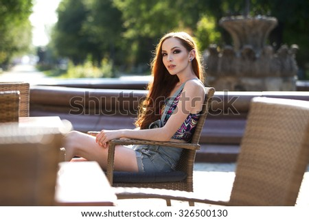 Beautiful young redhead outdoors - stock photo