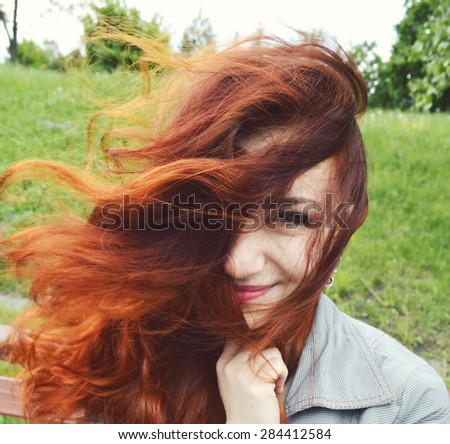 Beautiful young redhead woman smiling with closed eyes, enjoying nature, relaxing, meditating.beautiful hair fluttering in the wind - stock photo
