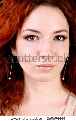 Beautiful young redhead woman with perfect daytime makeup and long silver earrings smiling - stock photo