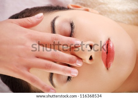 Beautiful young relaxed woman enjoy receiving face massage at spa saloon - stock photo