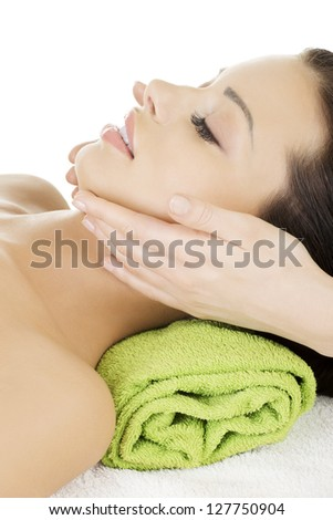 Beautiful young relaxed woman enjoy receiving face massage therapy at spa saloon - stock photo