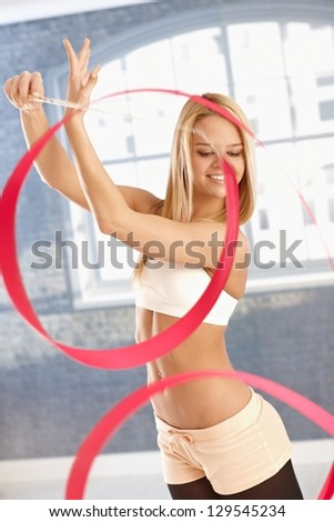 Beautiful young rhytmic gymnast girl exercising with ribbon, smiling happy. - stock photo