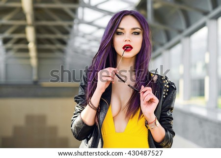 Beautiful young rock style girl in yellow swimsuit and purple hair posing and having fun on the urban background outdoor summer
