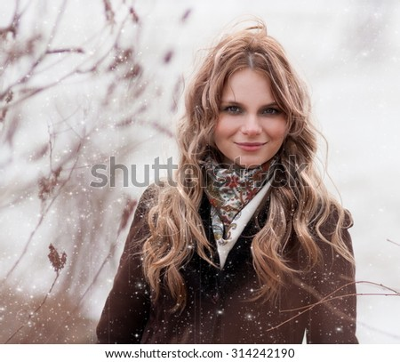 Beautiful young romantic elegant blonde woman face, has gray eyes, sexy lips, happy fun smile, curly  hair, brown coat. Pure makeup. White background. Winter snow day. Christmas holiday. - stock photo