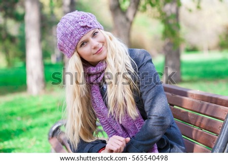 Beautiful young romantic elegant blonde woman face, has gray eyes, sexy lips, happy smile, nature long hair, gray woolen coat, lilac hat and scarf. Pure makeup. Spring day. Close up.